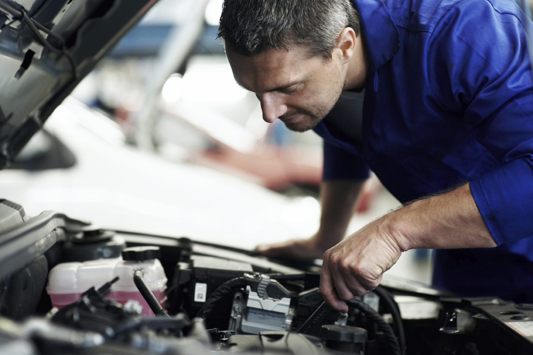 Closeup of an experienced mechanic servicing a car at his workshop - Copyspace